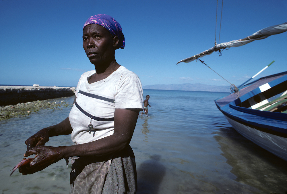 Haiti, Île de la Gonave, Woman cleans freshly caught fish along shoreline in small island town of Anse-a-Galets