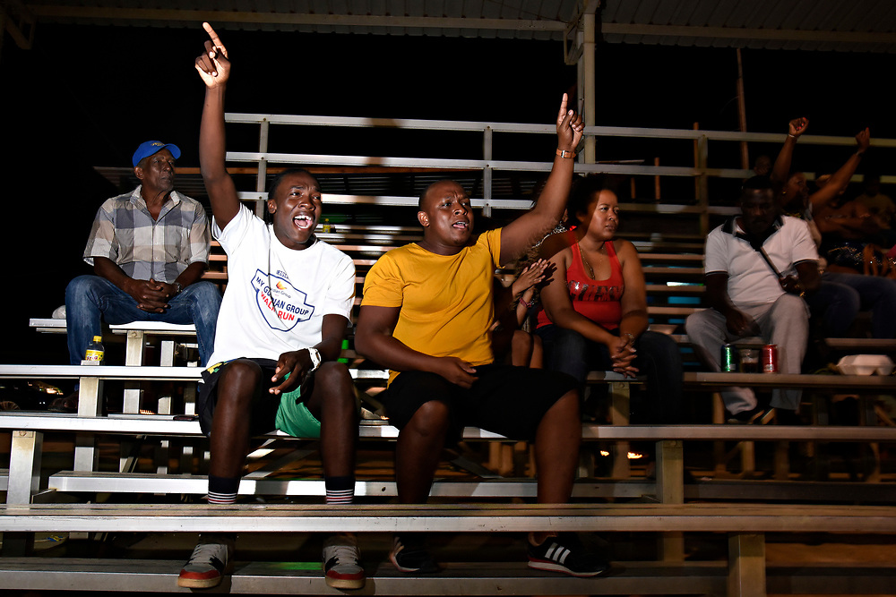 "WILLEMSTAD, CURACAO - DECEMBER 12, 2014: Brothers Rody Welvaart, 18, left, and Sandy Welvaart, 30, cheer on their favorite local team during a Liga Vruminga tournament at the Frank Curiel field. They both grew up playing baseball and still love the game. Sandy says he grew up being a big fan of Hensley ""Bam-Bam"" Meulens, and loves seeing all the young players following in his footsteps by playing Major League Baseball. (photo by Melissa Lyttle)"