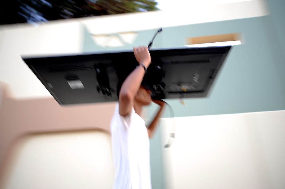A libyan man carries a flat screen TV looted from one of the buildings at Muammar Gaddafi's Bab Al Azizia compound in Tripoli.