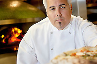 Close-up of a confident chef with pizza