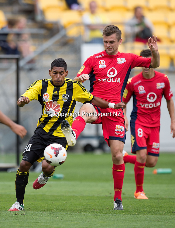Wellington Phoenix's Roy Krishna (L) fights for possession with Adelaide United's Cameron Watson during the A-League - Phoenix v Adelaide Utd soccer match at the Westpac Stadium in Wellington on Sunday the 30th March 2014.  Photo by Marty Melville/Photosport.co.nz
