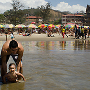 A father and son playing in the surf on the beach in Montañita, Ecuador.