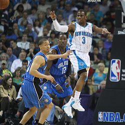 18 February 2009: New Orleans Hornets guard Chris Paul (3) passes the ball away from Orlando Magic defenders Tyronn Lue (10) and Dwight Howard (12)during a NBA basketball game between the Orlando Magic and the New Orleans Hornets at the New Orleans Arena in New Orleans, Louisiana.