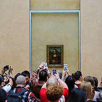 Dozens of visitors clamor to get a glimpse and a photograph of The Mona Lisa, on display at The Louvre in Paris, France, in April, 2015.