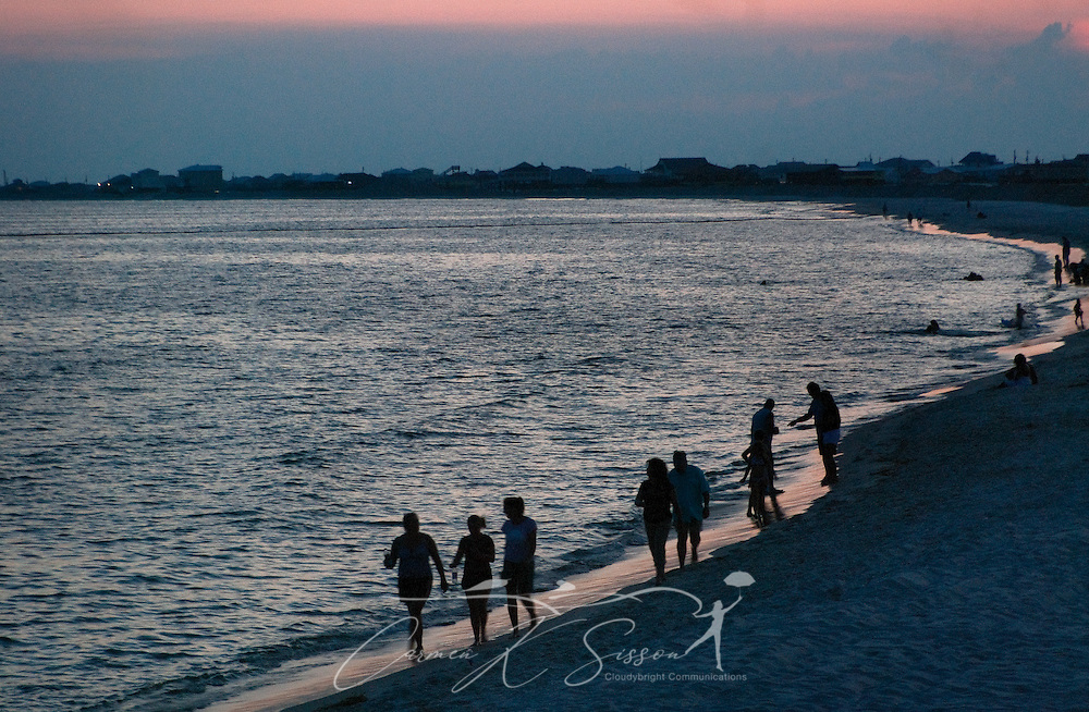 People gather along the shoreline at sunset in Dauphin Island, Ala. Oil continues to spill into the Gulf of Mexico following the April 20, 2010 explosion of the Deepwater Horizon oil rig, fouling marshes and beaches along the Louisiana, Mississippi, Alabama, and Florida coastline. Tar balls have been found on Dauphin Island beaches, but so far the area has avoided more serious consequences. (Photo by Carmen K. Sisson/Cloudybright)