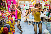 "03 MARCH 2013 - BANGKOK, THAILAND:   NAM (left) and KWANT, (stage names) ""coyote dancers"" from the Never Die dance troupe, perform for Chuchok while women eat their lunch. The Chuchok Shrine is in suburban Bangkok. More than 100 people a week come to the shrine to pray for good fortune or good health. People whose prayers are answered return to the shrine with ""coyote dancers"" to make merit and thank Chuchok. Coyote dancing is a Thai phenomenon created after the US movie ""Coyote Ugly"" where attractive young women dance in a sexually suggestive way, usually for pay. They're common at bars and festivals. Coyote dancers are typically better paid than other Thai women in the hospitality industry and usually are not allowed to date or see customers are off the dance floor. Coyote dancers perform at the Chuchok shrine because according to Buddhist literature Chuchok was a relatively repulsive old hermit and Brahmin priest who was cared for by a young woman after he made her family's wishes come true. PHOTO BY JACK KURTZ"