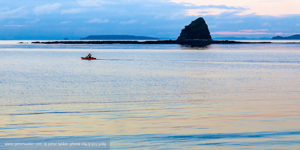 A kayaker setting out for their fishing spot off Sullivans Bay, Hauraki Gulf, New Zealand. The end of Whangaparaoa Peninsula and Tiritiri Matangi Island are visible in the distance, behind the silhouette of Pudding Island.
