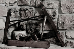 28 January 2012:    antique crockery and tools including a bow saw, jack, plane, hammer and keyhole saw are displayed on a stone hearth