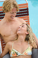 Young Couple on Sunlounger by Pool