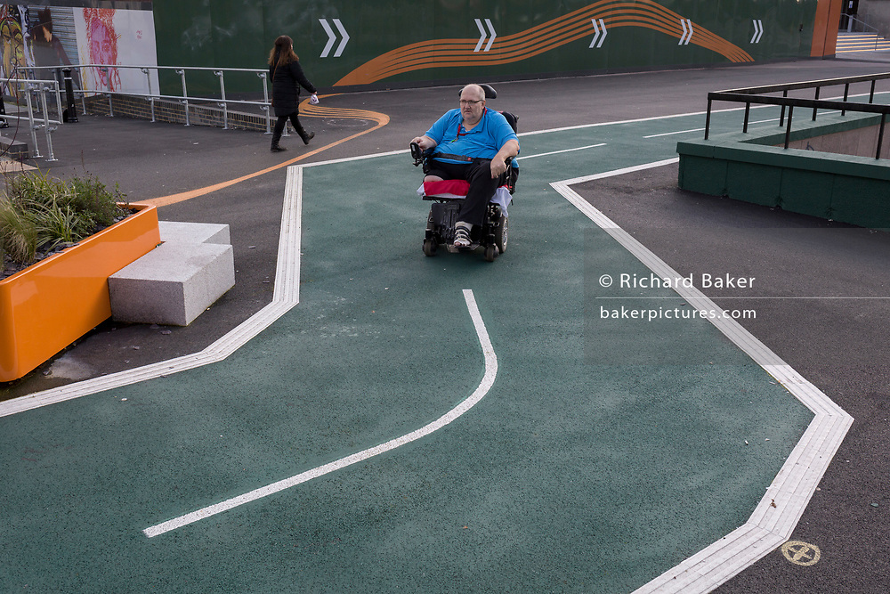 A disabled man travels in his motorised wheelchair on a new cycling path, a regenerated landscape created outside Croydon College and Fairfield Hall, on 20th January 2020, in Croydon, London, England.