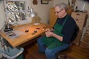 Boston violin maker Christopher White uses a tapering tool to precisely shape a tuning peg.