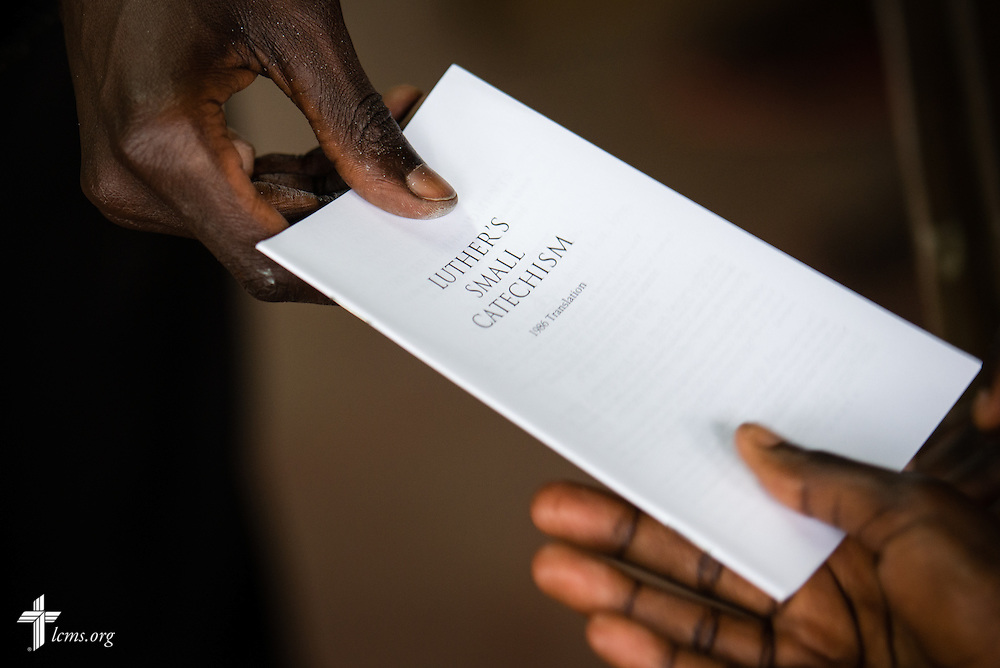 The Rev. Edwin Ogutta of the Mamboleo parish hands out Luther's Small Catechism during catechism class at the Tumaini ELCK (Evangelical Lutheran Church in Kenya) Project 24 boarding facility on Sunday, Oct. 18, 2015, in Kisumu, Kenya. LCMS Communications/Erik M. Lunsford