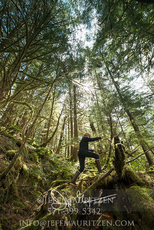 A woman hikes through the forest of Lowe Inlet Marine Provincial Park, British Columbia, Canada.