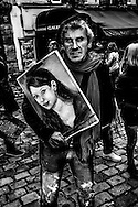 """March 2015. Paris. An artist holding a girl's portrait in Montmartre. They do a """"souvenir"""" portraits fort the big amount of  tourists who visit each day this famous district of Paris."""