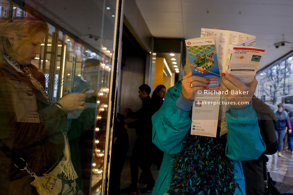 A poor-sighted shopper examines close-up a map of central London while shopping in Oxford Street.