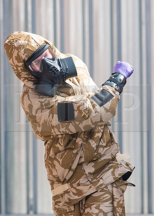 © Licensed to London News Pictures. 06/07/2018. Salisbury, UK. A member of a military specialist team wearing a hazmat suit is seen leaving John Baker House in Salisbury, Wiltshire an area visited by two people who are in critical condition after being exposed to the Novichok nerve agent. Dawn Sturgess, 44, and Charlie Rowley, 45 have been confirmed as having come in to contact with the deadly agent after samples were sent to the MoD's Porton Down laboratory. Former Russian spy Sergei Skripal and his daughter Yulia were poisoned with Novichok nerve agent in nearby Salisbury in March 2018 causing diplomatic tentions between Russia and the UK. Photo credit: Ben Cawthra/LNP