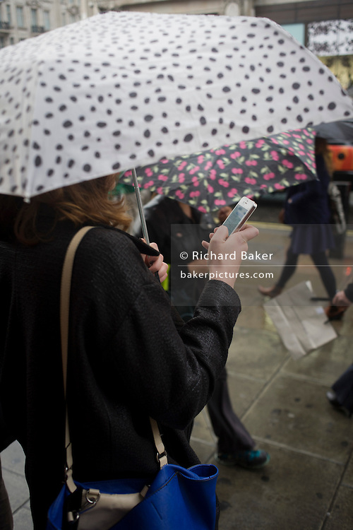 A woman uses her smartphone during autumnal rain in central London's Oxford Street.