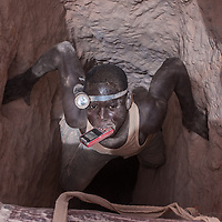 Nobsin, Burkina Faso - 13 May 2014: a young man wearing a forehead torch holds his mobile phone in his mouth as he descends in a 25 meters mine shaft. In the around 700-800 artisanal sites around the country, there's no health and safety, no hard hats or harnesses, no protective masks, no lights and no decent ventilation system.