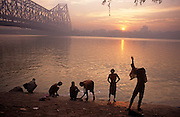 It is dawn in Calcutta, West Bengal, India and on the West bank of the Hooghly River the sun is rising from across the Howrah Bridge. Six bathers are either drying themselves after washing in the river, or are undressing to do so. It is a scene of inner-peace, a tranquillity surrounded by the chaotic pace of Indian life in this city. The engineering of the bridge stretches across the water towards the city beyond. The bridge is one of three on the Hooghly River and is a famous symbol of Kolkata and West Bengal. Bearing the daily weight of approximately 150,000 vehicles and 4,000,000 pedestrians. It is one of the longest bridges of its type in the world. The Hooghly River is an approximately 260 km long distributary of the Ganges River.