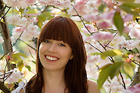 Smiling Young Woman by Fruit Tree