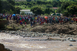 Residents wait on the other side of the river before crossing a mekshift bridge. Five days after tropical cyclone Idai cut a swathe through Mozambique, Zimbabwe and Malawi, the confirmed death toll stood at more than 300 and hundreds of thousands of lives were at risk, officials said.