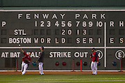 10/22/13 — BOSTON — Boston Red Sox outfielder Mike Carp, left, throws back to the infield as Quintin Berry and Daniel Nava look on during workouts for the World Series at Fenway Park on Oct. 22, 2013.