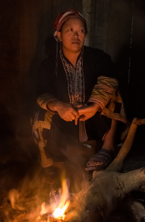 SAPA, VIETNAM - CIRCA SEPTEMBER 2014:  Woman from the Red Dao minority with fire pit inside a home in Ta Phin Village near Sapa, north Vietnam.