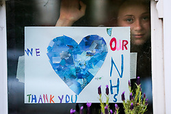 "© Licensed to London News Pictures. 23/04/2020. London, UK. A girl looks out of the window next to ""WE THANK YOU OUR NHS' drawing displayed in a house in north London. Rainbows are used as a symbol of peace and hope. Photo credit: Dinendra Haria/LNP"
