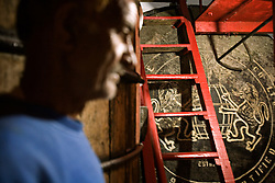 An employee examines whisky barrels stored in a cellar, Rawalpindi, Pakistan, Sept. 12, 2007.