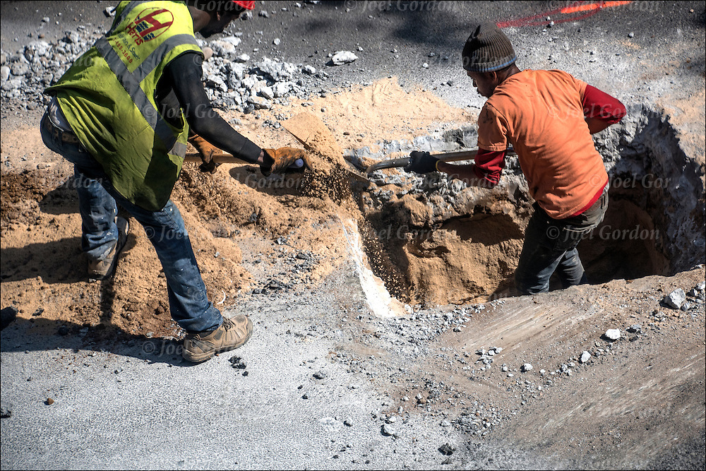 African American blue collar workers digging up  New York City street for replacement new water pipes.