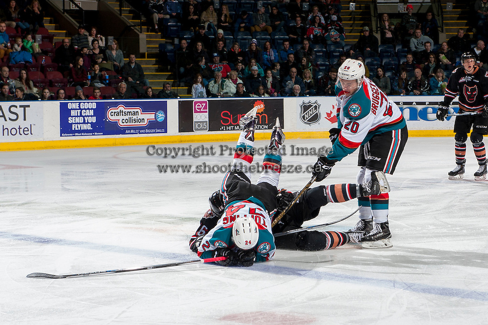KELOWNA, CANADA - FEBRUARY 1: Jake Kryski #16 of the Calgary Hitmen is checked by Conner Bruggen-Cate #20 as Kyle Topping #24 of the Kelowna Rockets tumbles to the ice during second period on February 1, 2017 at Prospera Place in Kelowna, British Columbia, Canada.  (Photo by Marissa Baecker/Shoot the Breeze)  *** Local Caption ***