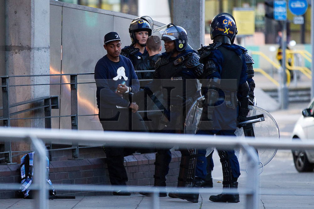 © Licensed to London News Pictures. 09/08/2011. Manchester, UK. Destruction and looting  across the city centre by gangs. Shops are smashed, looted. A man is arrested outside the Arndale Centre. Photo credit : Joel Goodman/LNP
