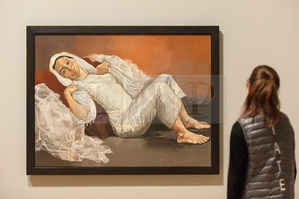 "© Licensed to London News Pictures. 26/02/2018. LONDON, UK. A staff member views ""Bride"", 1994, by Paula Rego. Preview of ""All Too Human"", an exhibition at Tate Britain which explores how artists in Britain have stretched the possibilities of paint in order to capture life around them.  The exhibition runs 28 February to 27 August 2018 and includes rarely seen works by Lucian Freud and Francis Bacon.  Photo credit: Stephen Chung/LNP"