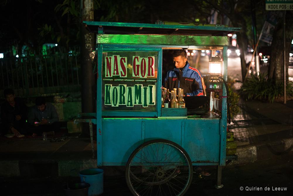 Man verkoopt nasi goreng 's avonds op straat in Malang.