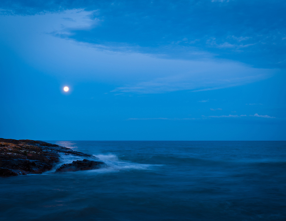The soft twilight envelopes the Minnesota shoreline as the moon rises over Lake Superior.