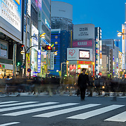 A busy intersection in Shinjuku during rush hour in Tokyo.