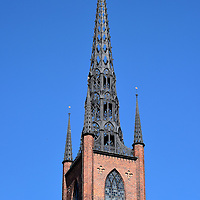 Riddarholm Church Spire in Stockholm, Sweden <br /> Riddarholm Church was constructed in the late 13th century making it one of Stockholm's oldest buildings.  It did not have a tower when it was built as a monastery.  In 1581, King John III hired Willem Boy, a prolific architect at the time, to create a spire. After it was destroyed by lightening in 1835, this cast iron version was added.  Notice the diamond-shaped design that turns blue against the sky.