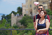 MONACO, MONACO - JUNE 17, 2015: Unidentified asian couple make selfie with a smartphone on a stick at the viewpoint in Monaco.