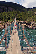Four year old Dixie Conrow crosses the swinging bridge over the Kootenai River at Kootenai Falls in Lincoln County, northwest Montana.