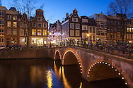 Houses and a canal bridge illuminated at night, Amsterdam. Christmas decorations hang over the street. http://www.gettyimages.com/detail/photo/bright-lights-big-city-royalty-free-image/481202095