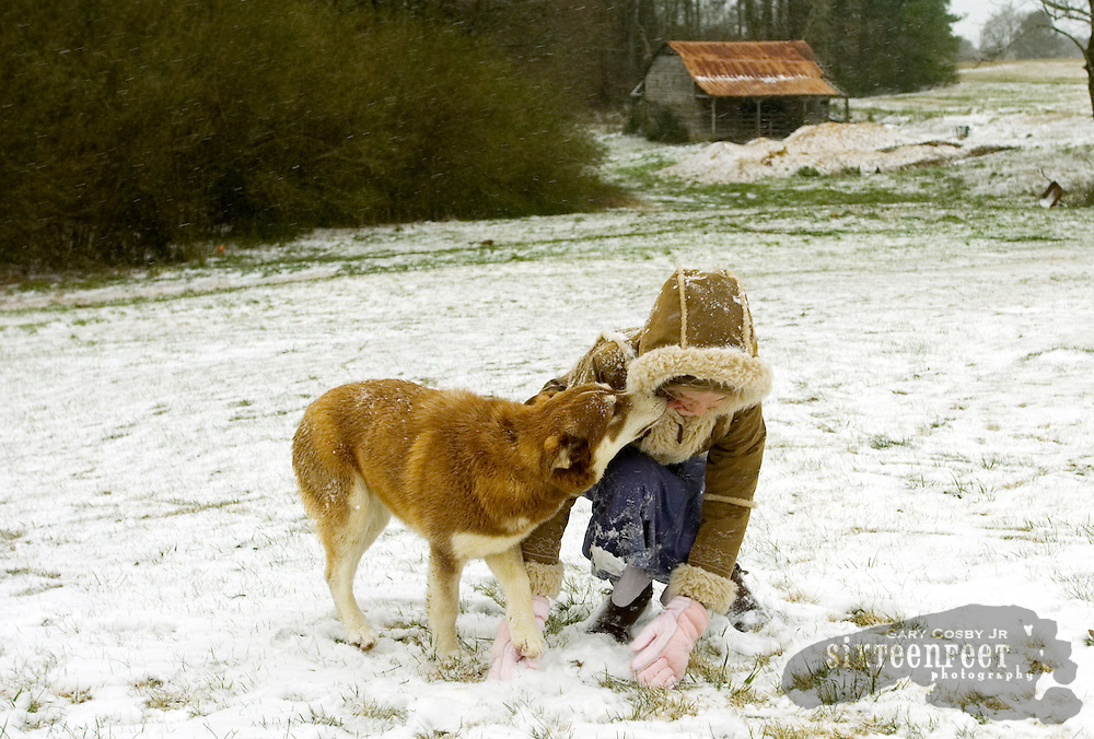 Morghann Brand, 10, gets a kiss from her dog Coco while making snowballs at her home on Brindlee Mountain in eastern Morgan County, AL Saturday, March 8, 2008.  North Alabama felt only the slightest bite from a winter storm that dumped heavy snow across much of the midwest and northeast.  Photo by Gary Cosby Jr.