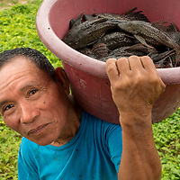 A Peruvian fisherman smiles while holding a red plastic bucket of catfish in the village of San Francisco off of the Marañon River. Pacaya Samiria National Reserve, Upper Amazon, Peru.
