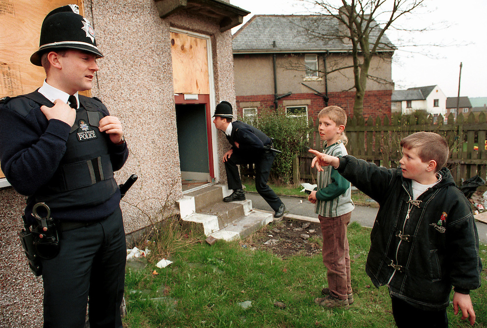 Young boys talk to police on a rundown housing estate in Leeds in Yorkshire, UK.