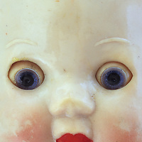 Close up of face of vintage baby doll with big staring blue eyes and red lips and slightly scuffed and soiled