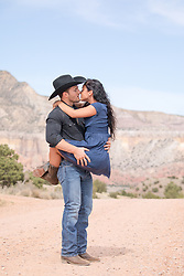 cowboy holding a girl off the ground outdoors