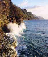 I climbed up a rock cliff to photograph this wave breaking on the Na Pali Coast.  The blue green surf has some fine detail and the view down the coastline is magnificent.