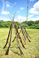 Old Bethpage, New York, USA - July 21, 2012: Stacks of Civil War rifles with attached bayonets are lines up, with American flag at rear, at re-creation of Camp Scott, a Union Army training camp, Old Bethpage Village Restoration, to commemorate 150th Anniversary of American Civil War, on Saturday, July 21, 2012.
