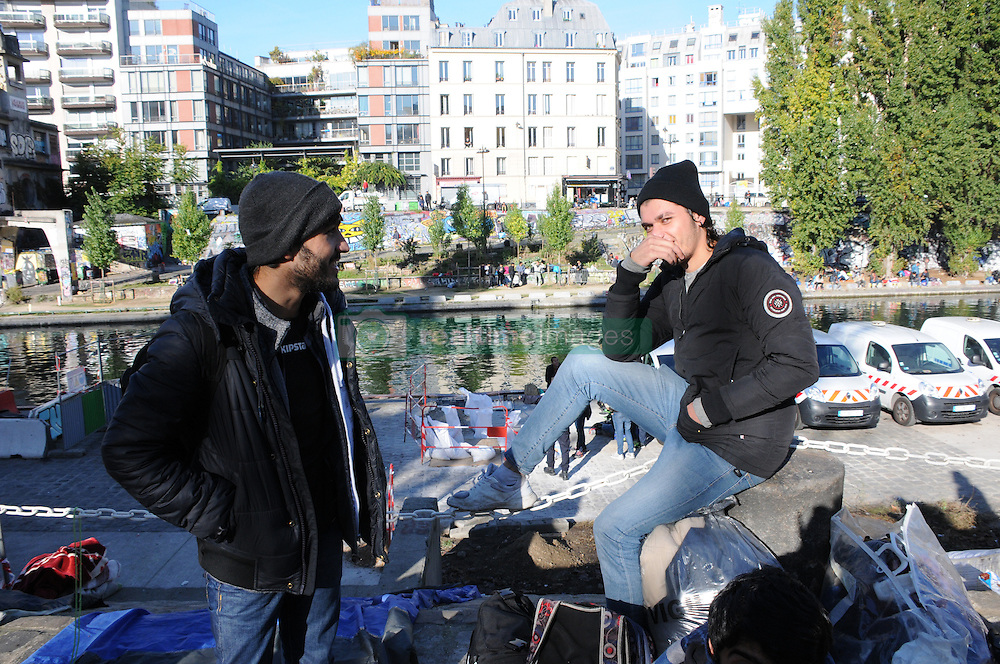 """Migrants stand at the Canal Saint-Martin, near the Jaures and Stalingrad metro stations, in northern Paris, France, on October 31, 2016, during a police operation aiming at a future evacuation of a migrant camp. An operation of """"administrative control"""" was underway on early October 31 in the Jaures/Stalingrad quarter before a future evacuation, whose date has not yet been set, according to a police source. The makeshift camp on the outskirts of the 10th and 19th arrondissements in the north of the capital numbers today 2,500 people, according to the City of Paris. Photo by Alain Apaydin/ABACAPRESS.COM"""