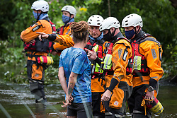 Denham, UK. 24 July, 2020. Police officers from Hampshire Police Marine Support Unit ask a female activist from HS2 Rebellion to move out of the river Colne where she had been trying to hinder the destruction of an ancient alder tree in connection with works for the HS2 high-speed rail link in Denham Country Park. A large policing operation involving the Metropolitan Police, Thames Valley Police, City of London Police and Hampshire Police as well as the National Eviction Team was put in place to enable HS2 to remove the tree.