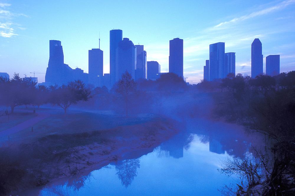 Blue silhouetted Houston, Texas skyline from a foggy Buffalo Bayou.